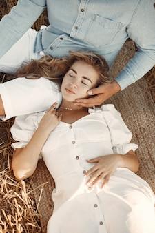 밀밭에 앉아 젊은 부부의 닫습니다. 사람들은 초원에 건초 더미에 앉아 포용합니다.