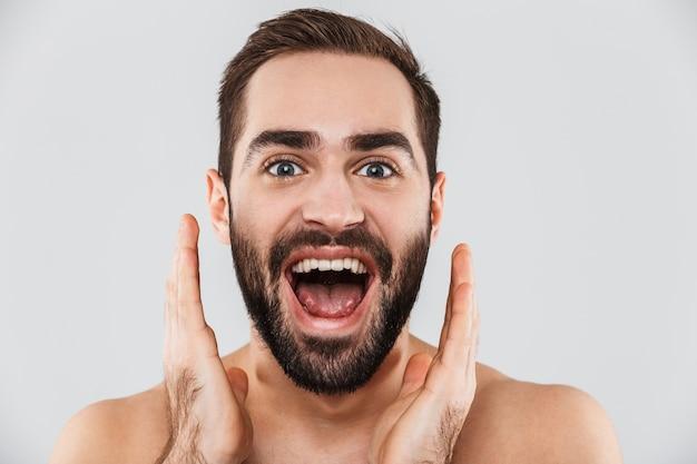 Крупным планом молодой возбужденный красивый бородатый мужчина без рубашки, стоящий изолированно над белой