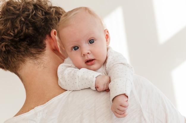 Крупным планом молодой отец, держащий своего маленького сына, стоя в помещении, ребенок смотрит прямо