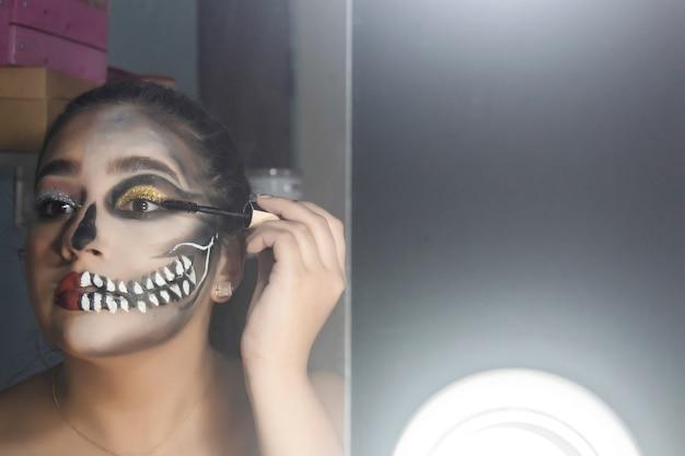 Крупный план молодой девушки, поднимающей ресницы, макияж на хэллоуин, сделанный в ее комнате.