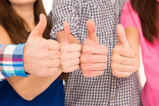 Крупным планом молодая группа показывает палец вверх
