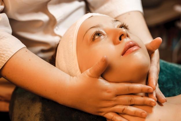 Крупным планом молодая прекрасная женщина расслабляется во время массажа лица в оздоровительном спа-центре.