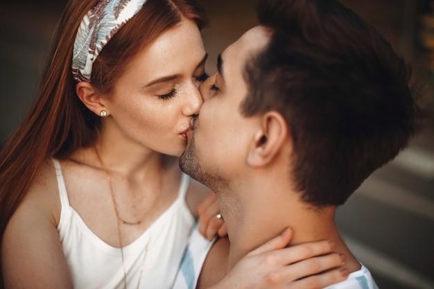 Закройте молодые влюбленные поцелуи с закрытыми глазами. очаровательная молодая женщина с рыжими волосами и веснушками целует своего парня на улице во время свиданий.