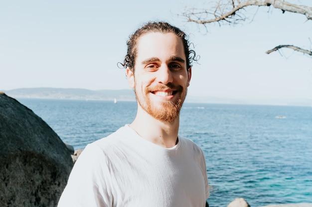 Крупным планом молодой мужчина с пустой белой рубашкой, улыбаясь в камеру на побережье испании во время пляжного дня, концепция счастья психического здоровья