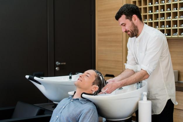 Крупный план молодого человека, его волосы моют в парикмахерской