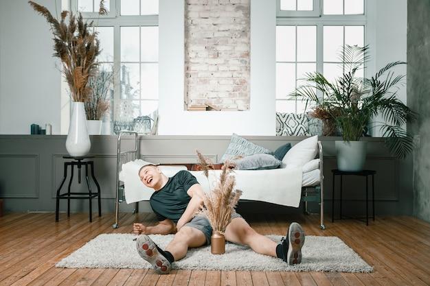 스포츠 유니폼을 입은 젊은 남자의 근접 촬영은 집에서 바닥에 쉬고, 카메라를보고 침실에 smillling