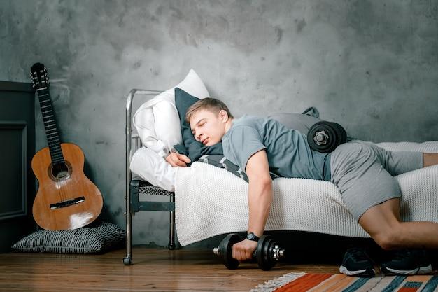 스포츠 유니폼을 입은 젊은 남자의 근접 촬영은 아령으로 침대에서 자고 쉬고 있습니다. 선수 휴게실 및 운동 연기