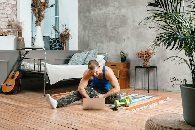 スポーツユニフォームを着た若い男性のクローズアップが休んでいる、自宅の床に伸びている、映画を見ている、ラップトップ、ソーシャルネットワークから勉強している