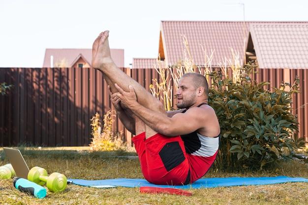 スポーツユニフォームを着た若い男性のクローズアップは、夏に裏庭の床に伸びて、難しい位置で瞑想しようとします