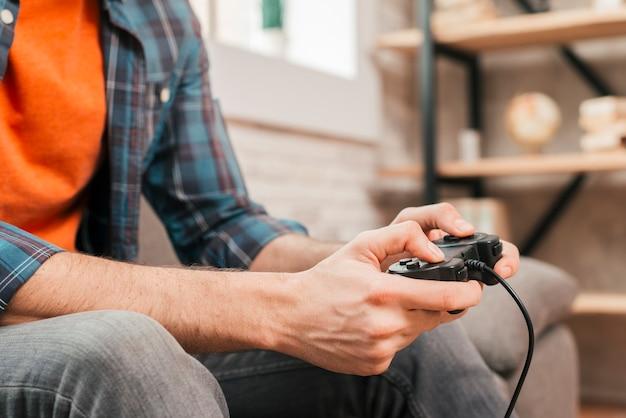 Крупный план молодого человека, играющего в игровую приставку у себя дома