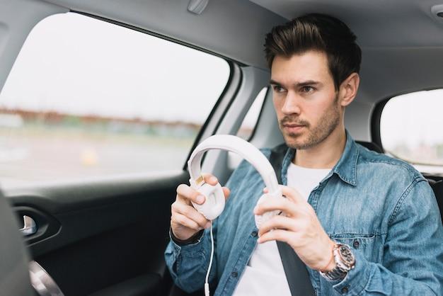 白いヘッドフォンを置く車で旅行している若い男のクローズアップ