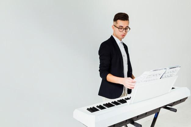 피아노에 뮤지컬 시트의 페이지를 선회하는 젊은 남자의 근접 흰색 배경에 고립