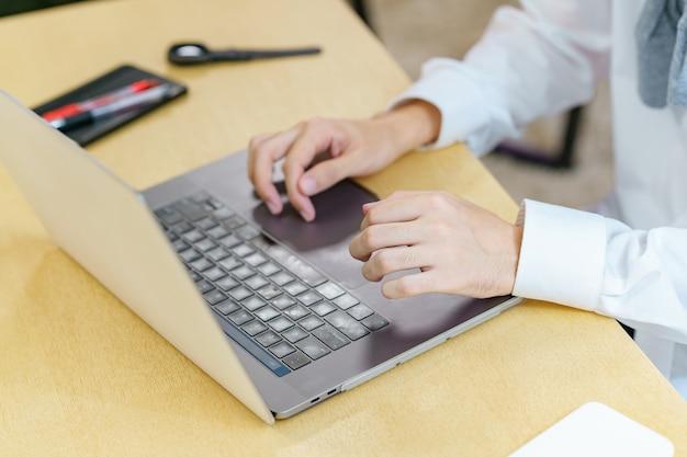 캐주얼한 공간에서 노트북을 사용하는 젊은 남자의 클로즈업