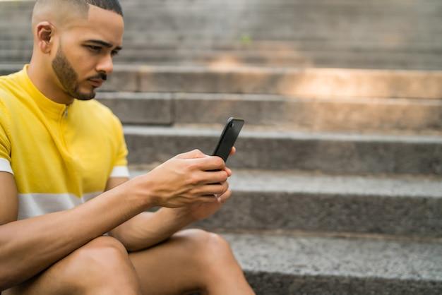 通りの屋外のコンクリートの階段に座っている間彼の携帯電話を使用して若い男のクローズアップ。コミュニケーションの概念。