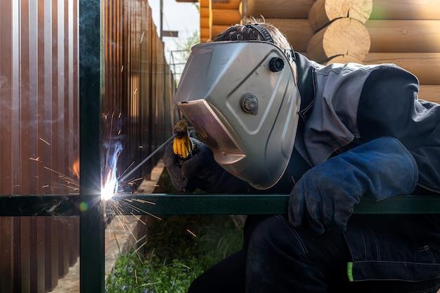 制服、溶接マスクと溶接機の革、溶接金属の若い男の溶接工のクローズアップ