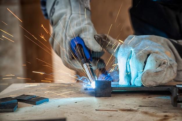 アーク溶接機で金属を均一に溶接する若い男の溶接工の接写