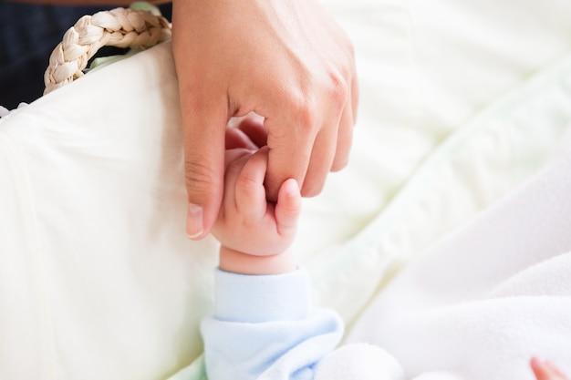 Крупный план молодой матери, держащей руку своего ребенка, лежащего на его колыбели