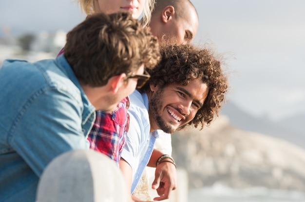 ビーチの近くで友達と楽しんでいる若い多民族の男のクローズアップ