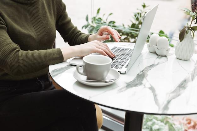 Крупным планом молодая рыжая женщина расслабляется за столиком в кафе в помещении, пьет кофе, работает на портативном компьютере