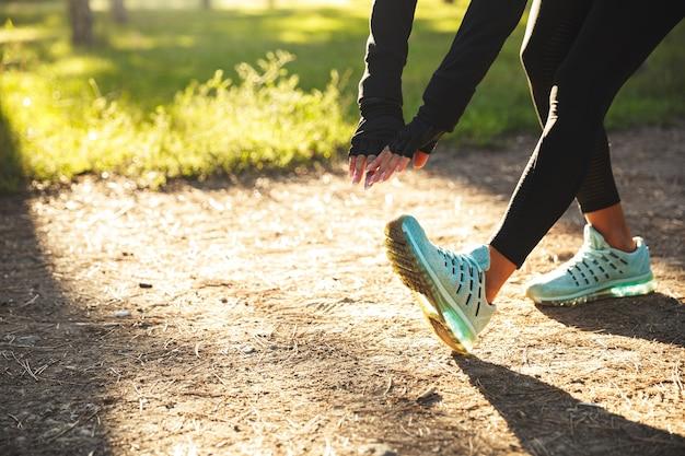 Крупным планом молодой спортивной женщины, делающей упражнения на растяжку перед бегом на открытом воздухе