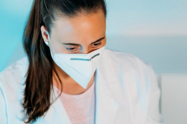 Закройте доктора молодой женщины в белом халате на рабочем месте с маской для защиты от коронавируса