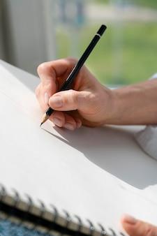Крупный план молодой женщины, рисующей дома у окна