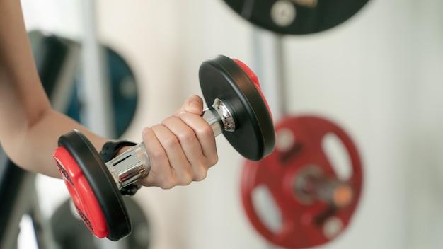 Крупный план молодой женщины, тренирующейся с весами в тренажерном зале.