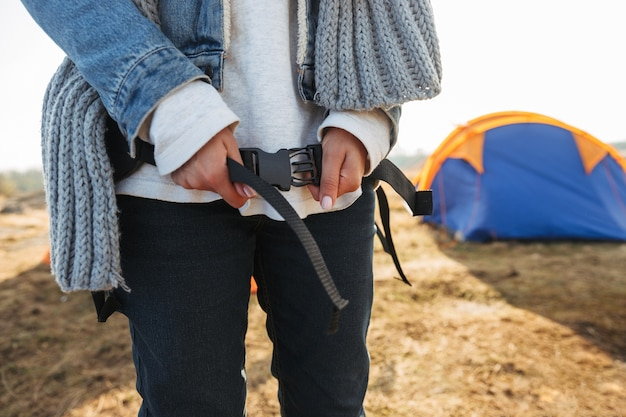 캠프장에 서서 하이킹을 준비하는 젊은 여자의 닫습니다