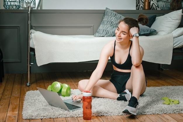 スポーツユニフォームを着た若い女性のクローズアップが自宅の床で休んでいる、映画を見ている、ラップトップ、ソーシャルネットワークから勉強している