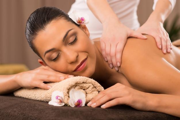 Крупный план молодой женщины, получающей массаж спины в спа-салоне