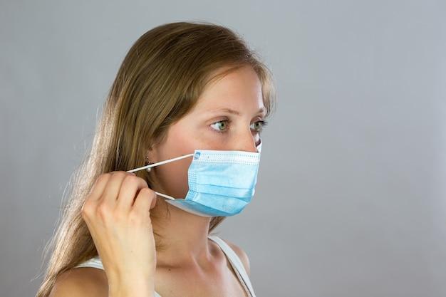 머리에서 얼굴 마스크를 제거하는 젊은 여자의 근접 촬영