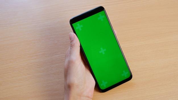 垂直の緑色の画面でスマートフォンとテーブルで若い女性の手のクローズアップ