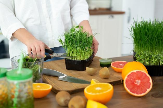 비타민 스무디를 만들기 위해 기성품 마이크로 녹색 완두콩을 자르는 부엌에서 젊은 여성의 손을 클로즈업합니다.