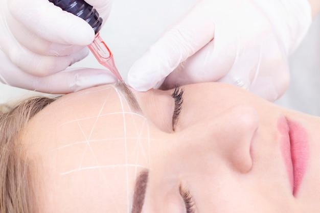Крупный план молодой женщины, проходящей перманентный макияж бровей в салоне красоты
