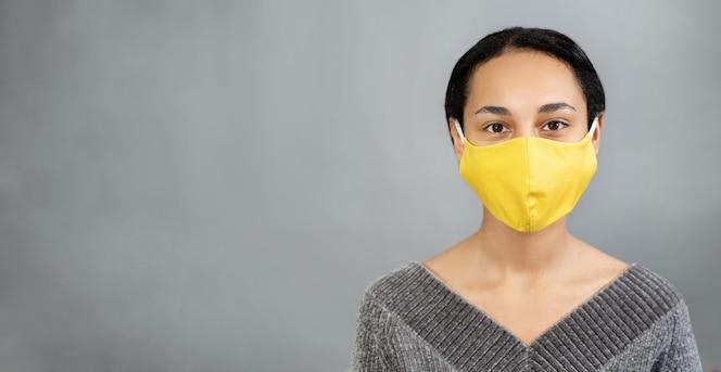 Sars-cov-2에 대한 그녀의 얼굴에 노란색 마스크를 가진 젊은 여자의 닫습니다. 회색 벽. 공간을 복사하십시오. 2021 년 컬러 트렌드. 긍정적 인 개념
