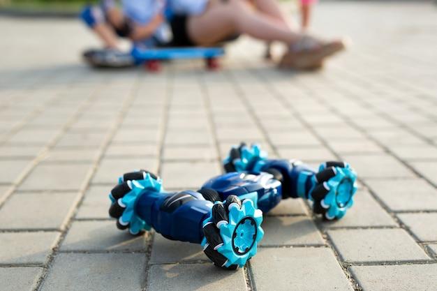 ロボットの車で遊んでいる子供たちと若い女性のクローズアップ。子供のための新しい技術玩具