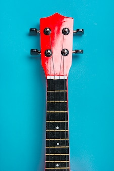 Close-up of acoustic classic guitar head on blue background