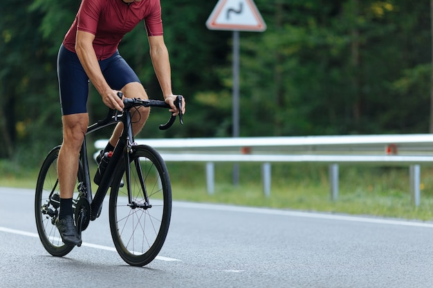 스포츠 의류 및 포장 도로에서 자전거를 타는 운동화에 적극적인 남자의 닫습니다. 근육질의 강한 다리에 집중