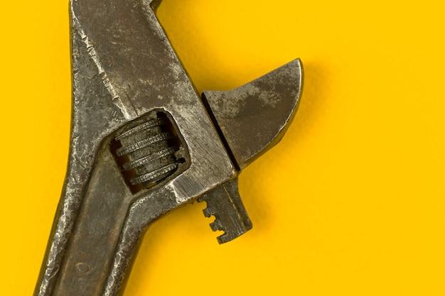 조정 가능한 렌치의 클로즈업, 오래된 그런지 수리 도구, 노란색 배경 사진