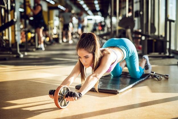 체육관에서 블랙 매트에 휠 롤러와 함께 사랑스러운 집중된 매력적인 스포티 한 피트니스 소녀 운동의 닫습니다.