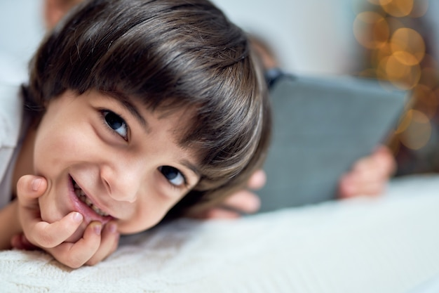 그의 형제와 시간을 보내는 동안 카메라를 보고 웃고 있는 사랑스러운 작은 라틴 소년의 클로즈업, hristmas로 장식된 집의 침대에 누워 있습니다. 어린이, 겨울 방학 개념