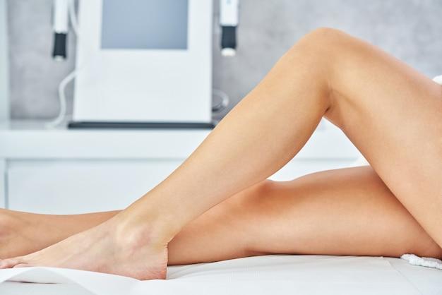 Крупный план взрослой женщины, ожидающей лазерной эпиляции ног в профессиональном салоне