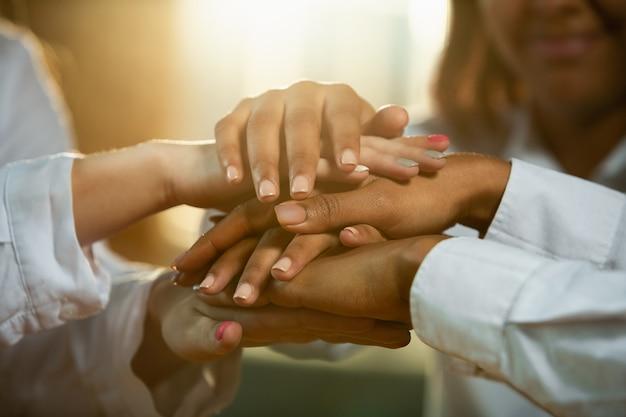나무 탁자를 잡고 있는 아프리카계 미국인과 백인 인간의 손을 닫습니다. 우정, 단결, 가족, 팀워크 또는 여성 권리의 제스처로 만지는 여성의 손.