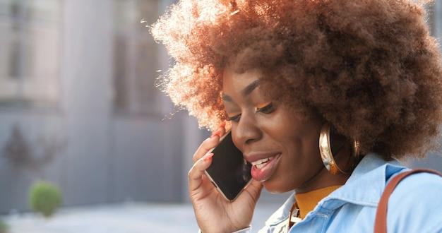 外の携帯電話で話しているアフリカ系アメリカ人の美しい幸せな笑顔の女性のクローズアップ。携帯電話で話し、笑顔の陽気な女性。素敵な電話での会話。