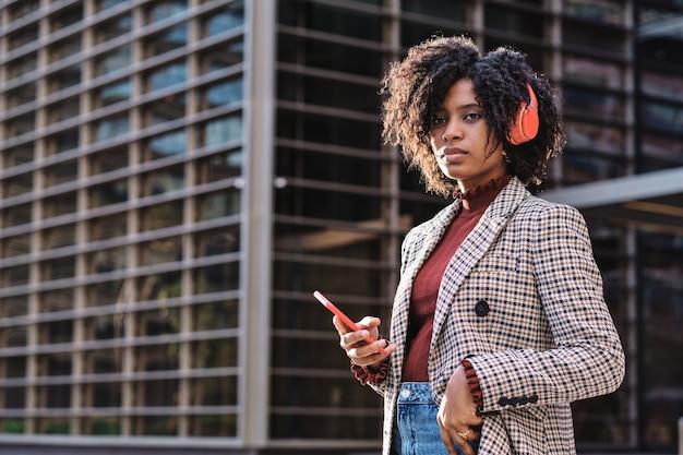 オフィスビルの外で仕事を休んでヘッドフォンと携帯電話で音楽を聴いているアフリカ系アメリカ人のビジネスウーマンのクローズアップ。