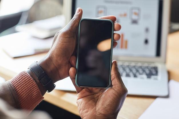 빈 검은 화면, 모바일 앱, 온라인 뱅킹 개념, 복사 공간이 있는 스마트폰을 들고 있는 아프리카계 미국인 사업가 클로즈업