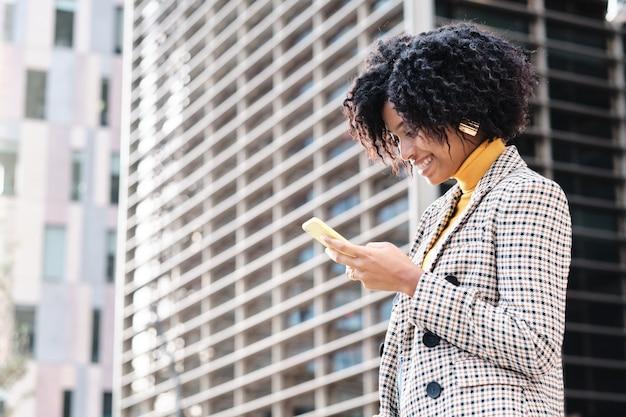 金融都市地区で働くために歩いている間彼女の携帯電話をチェックしているアフリカ系アメリカ人の実業家のクローズアップ。