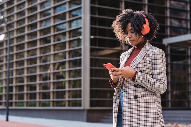 仕事に行く途中でヘッドフォンと携帯電話で音楽を聴いているアフリカ系アメリカ人の実業家のクローズアップ。