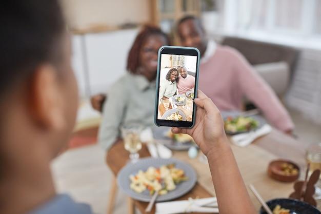 家のインテリアの夕食のテーブルで両親の写真を撮るアフリカ系アメリカ人の女の子のクローズアップ、スマートフォンの画面に焦点を当て、スペースをコピー