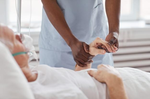 Крупным планом афро-американский медсестра, держащая за руку старшего человека в больнице и утешая его, копирование пространства